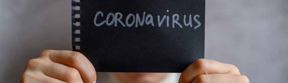 coronavirus-text-in-white-letters-on-a-black-notebook-paper-in-the-hands-of-a-woman-covers-her-face_t20_rRaYxd